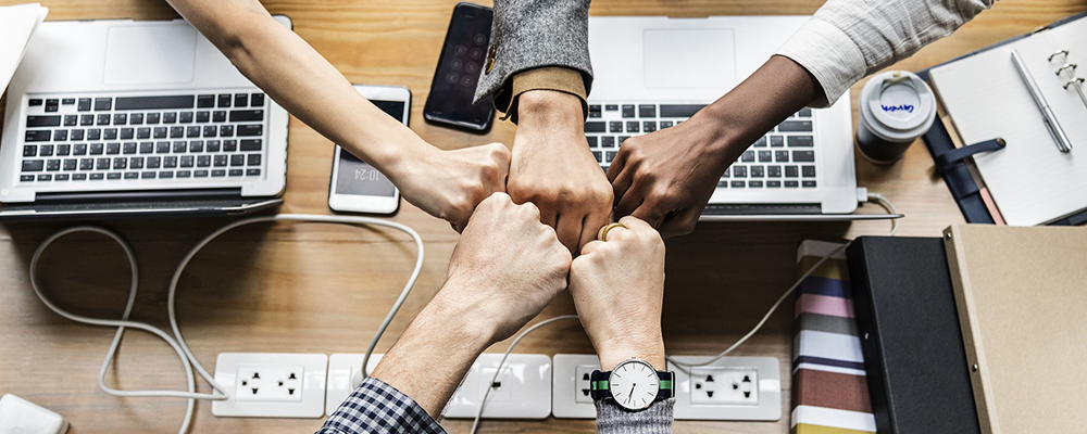 five employees fist-bumping at their desk