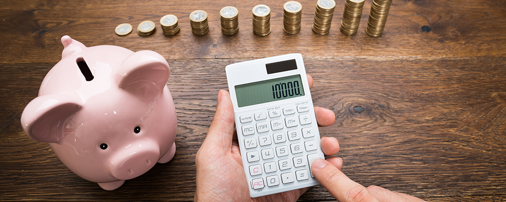 freelancer calculating pension savings with calculator and piggy bank