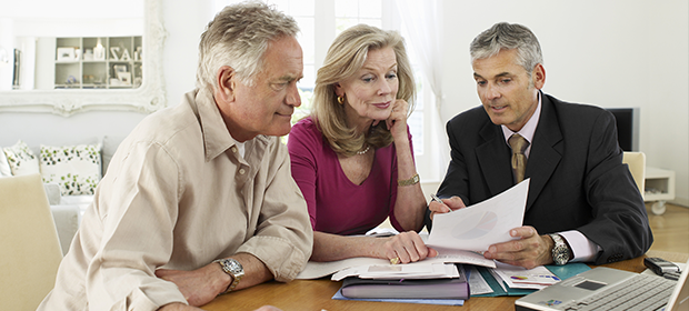 Couple sitting at table with accountant and paperwork