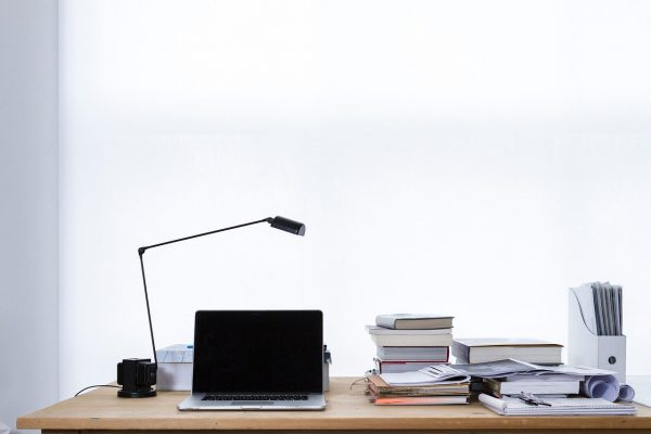 table with lamp books and laptop