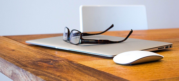 laptop and glasses on wooden desk