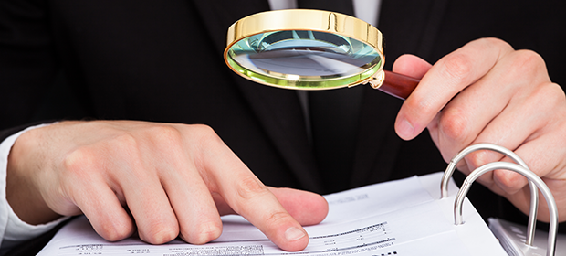 Legal professional examining a document with a magnifying glass